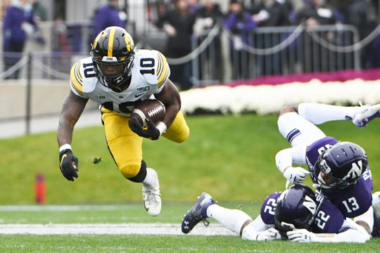 Iowa running back Mekhi Sargent picks up some of his 46 rushing yards in the first half against Northwestern on Saturday. He later scored from the 1-yard line to help the Hawkeyes polish off the Wildcats 20-0, ending a three-year skid in the rivalry.