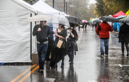 Guests and vendors battle heavy rain during the Irvington Halloween Festival in Indianapolis, Ind. on Saturday, Oct. 26, 2019.