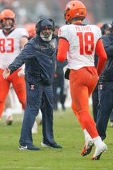 Fighting Illini coach Lovie Smith congratulates quarterback Brandon Peters (18) after Illinois scored a touchdown against the Purdue Boilermakers during the third quarter at Ross-Ade Stadium.