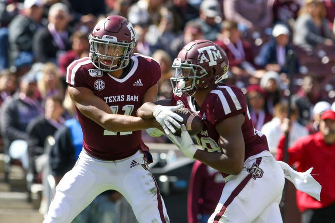 Oct 26, 2019; College Station, TX, USA; Texas A&M Aggies quarterback Kellen Mond (11) hands the ball off to Texas A&M Aggies running back Isaiah Spiller (28) during the third quarter against the Mississippi State Bulldogs at Kyle Field. Mandatory Credit: John Glaser-USA TODAY Sports