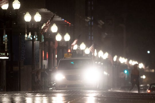 A pedestrian crosses Gay Street during an evening rain shower in Knoxville, Tennessee on Friday, October 25, 2019.