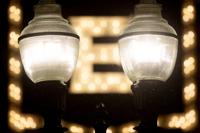 Rain drops fall on a light post in front of the Tennessee Theatre sign on Gay Street during an evening rain shower in Knoxville, Tennessee on Friday, October 25, 2019.