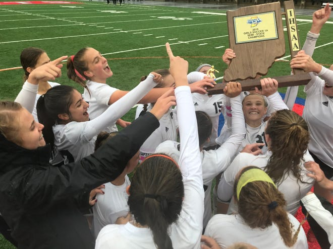 Central Catholic players raise the Class A semistate trophy after defeating Boone Grove 9-3 at Kokomo's Walter Cross Field on Saturday, Oct. 26, 2019.