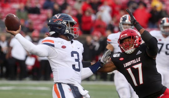 Louisville's Dorian Etheridge gets pressure on Virginia's Bryce Perkins on Oct. 26, 2019.
