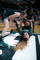 Michigan State's Kayla Belles, bottom, is congratulated by Claire Hendrickson, left, Nia Clouden, right, and Nia Hollie, rear, after hitting a three-quarter court shot during an NCAA college basketball scrimmage, Friday, Oct. 25, 2019, in East Lansing, Mich. (AP Photo/Al Goldis)