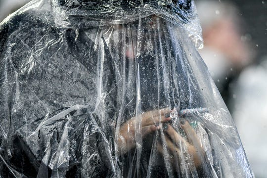 A Michigan State fans checks her phone under a rain pancho during the fourth quarter on Saturday, Oct. 26, 2019, at Spartan Stadium in East Lansing.