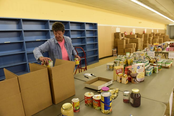 Vicki Todd stuffs boxes with thousands of donated cans of food Saturday during the Make A Difference Day food drive.