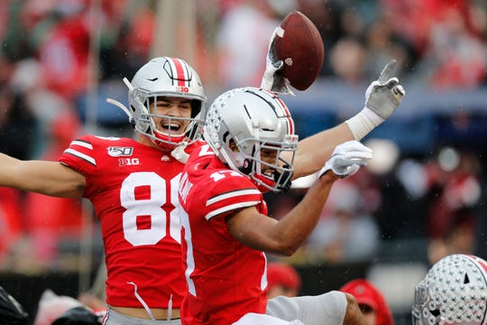 Ohio State receiver Chris Olave celebrates with tight end Jeremy Ruckert after making the first of his two touchdown catches in Saturday's 38-7 win over Wisconsin.