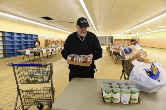 Rick Finnerty helps stack a pile of collected cans of food Saturday during the Make A Difference Day  food drive.