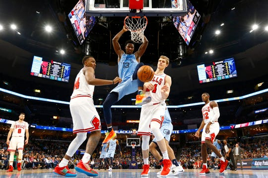 Memphis Grizzlies forward Jaren Jackson Jr. dunks the ball over Chicago Bulls forward Wendell Carter Jr., left, and Lauri Markkanen during the home opener at the FedExForum on Friday.