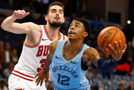Memphis Grizzlies guard Ja Morant slips past Chicago Bulls guard Tomas Satoransky on a drive to the rim during the home opener Friday.