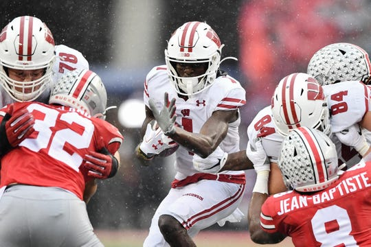 Aron Cruickshank of the Wisconsin Badgers looks for running room against Ohio State's defense in the third quarter.