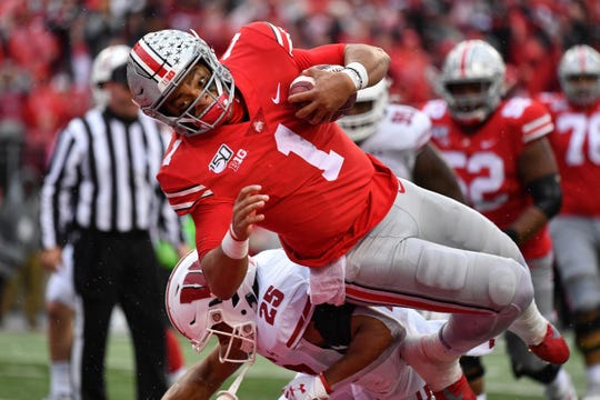 Justin Fields of Ohio State dives over Eric Burrell of Wisconsin for a 10-yard touchdown run in the third quarter.
