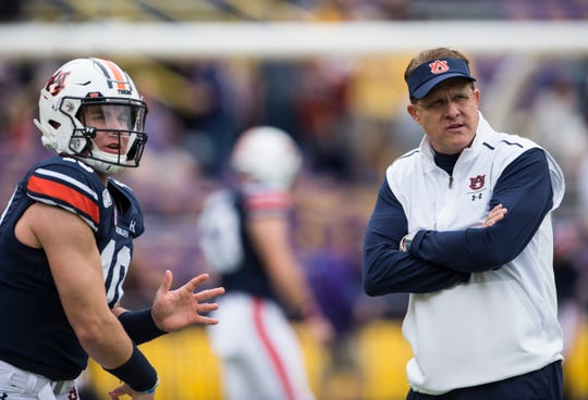 Auburn head coach Gus Malzahn talks with Auburn quarterback Bo Nix (10) during warm ups at Tiger Stadium in Baton Rouge, La., on Saturday, Oct. 26, 2019.