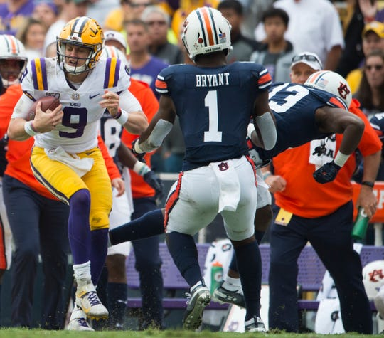 LSU quarterback Joe Burrow (9) spins out of the way of Auburn defensive back Javaris Davis (13) at Tiger Stadium in Baton Rouge, La., on Saturday, Oct. 26, 2019. Auburn and LSU are tied 10-10 at halftime.