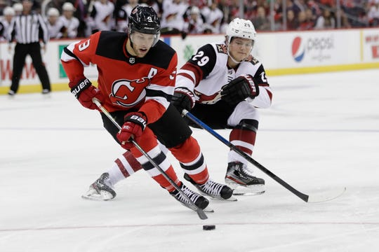 New Jersey Devils' Taylor Hall (9) fights for control of the puck with Arizona Coyotes' Barrett Hayton (29) during the first period of an NHL hockey game Friday, Oct. 25, 2019, in Newark, N.J.