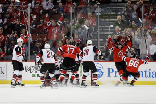 New Jersey Devils' Sami Vatanen, second from right, celebrates with Jack Hughes (86) after scoring a goal during the first period of the team's NHL hockey game against the Arizona Coyotes on Friday, Oct. 25, 2019, in Newark, N.J.