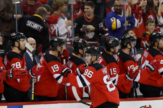 New Jersey Devils' Jack Hughes (86) celebrates with teammates after scoring a goal during the first period of the team's NHL hockey game against the Arizona Coyotes on Friday, Oct. 25, 2019, in Newark, N.J.