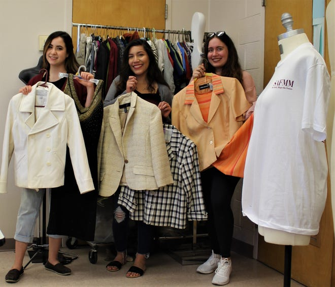 Student Association of Fashion Merchandising and Marketing President Savannah Willingham, Fundraiser Emily Soto, and Vice President Bethani Medrano show off just a few styles waiting to get upcycled — clothing that won't end up at landfills, and instead will find a new life in someone else's wardrobe.