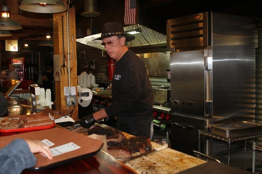 "Mad Jack's Mountaintop Barbecue owner James ""Jack"" Jackson slicing brisket for customers in Cloudcroft, NM."