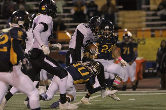 Piedra Vista's Jarrod Mitchell breaks a tackle for extra yards against Highland during Friday's District 1-5A football game at Milne Stadium in Albuquerque.