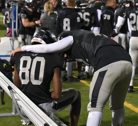 Wildcat lineman Austin Lazanja, right, consoles Ivan Davis who left the game late after re-injuring his knee.