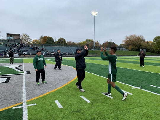 Novi's Blair Mayes high-fives coach Todd Pheiffer after winning the regional title.