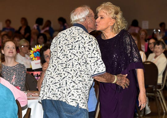 Kaye Ryder, a 14-year cancer survivor, receives a kiss from her husband, Jessie Ryder, as she strolls down the runway modeling the latest fashion at the 12th annual  Pink Bag Luncheon held Friday at the Evangeline Downs Event Center. The event was hosted by the Opelousas General Health System Foundation.