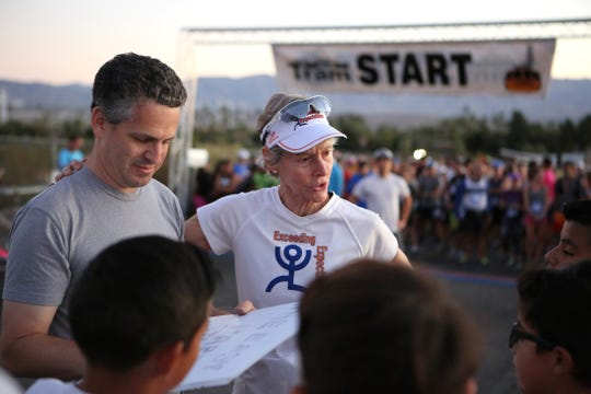 Tram Road Challenge race director Matthew Sills, left, and Exceeding Expectations director Cherie Gruenfeld, right, talk to the youth runners prior to the start of the 34th Annual Tram Road Challenge in Palm Springs, Calif., on Saturday, October 26, 2019.