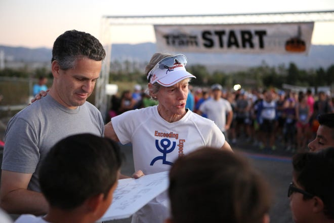 Tram Road Challenge race director Matt Sills, left, and Exceeding Expectations director Cherie Gruenfeld, right, talk to the youth runners prior to the start of the 34th Annual Tram Road Challenge in Palm Springs, Calif., on Saturday, October 26, 2019.