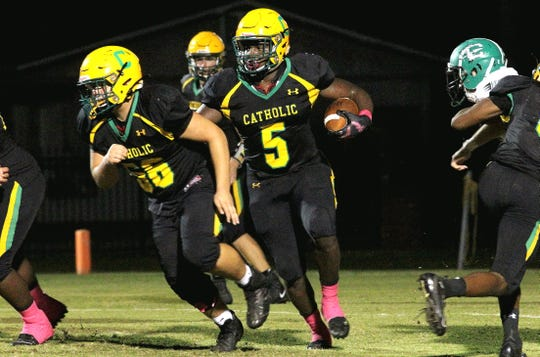 Ja'Kobi Jackson, who scored three of Catholics's touchdowns, runs through a big hole Friday in the Crusaders' win against Choctaw.