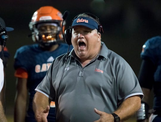 Head coach Mike Bennett communicates with his team during the Booker T. Washington vs. Escambia football game at Escambia High School in Pensacola on Friday, Oct. 25, 2019.