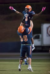 Chris Hale (3) is hoisted in the air by Brennan Smith (50) after scoring a touchdown and taking a 28-0 Gators lead (after adding the extra point) during the Booker T. Washington vs. Escambia football game at Escambia High School in Pensacola on Friday, Oct. 25, 2019.