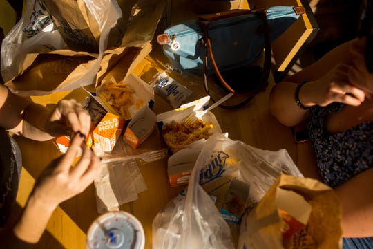 From left, Lindsey Wallace and Kjirsten Larson eat after waiting in line for three hours at White Castle Saturday, October 26, 2019 in Talking Stick Entertainment District near Scottsdale.