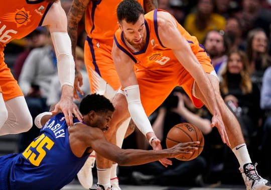 Denver Nuggets guard Malik Beasley (25) and Phoenix Suns forward Frank Kaminsky III (8) go after a loose ball during an NBA basketball game, Friday, Oct. 25, 2019, in Denver. Denver beat Phoenix 108-107 in overtime. (AP Photo/Jack Dempsey)