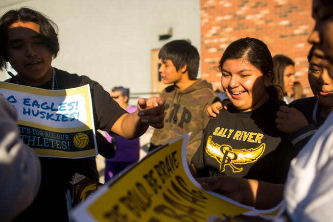 Hayden Hogue, a Salt River eighth-grader, helps hand out signs in support of Salt River High School before the continuation of the Caurus Academy game against Salt River High School Friday, Oct. 25, 2019, at Desert Heights Preparatory Academy in Glendale. The original game was halted Tuesday after reports of racial slurs against Salt River High School players.