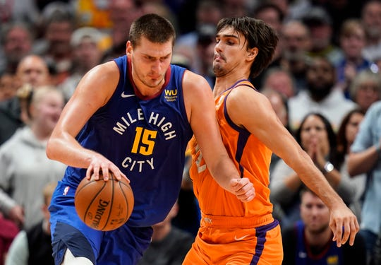 Denver Nuggets center Nikola Jokic (15) moves past Phoenix Suns forward Dario Saric (20) during overtime an NBA basketball game, Friday, Oct. 25, 2019, in Denver. Denver beat Phoenix 108-107 in overtime. (AP Photo/Jack Dempsey)