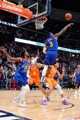 Denver Nuggets forward Torrey Craig (3) blocks a shot by Phoenix Suns' Devin Booker at the end of overtime in an NBA basketball game Friday, Oct. 25, 2019, in Denver. Denver won 108-107. (AP Photo/Jack Dempsey)
