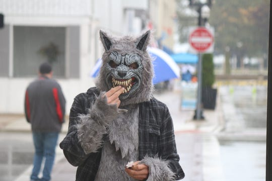 A werewolf roaming in downtown Port Clinton during the treat-or-treating on Saturday enjoys some candy along Madison Street.