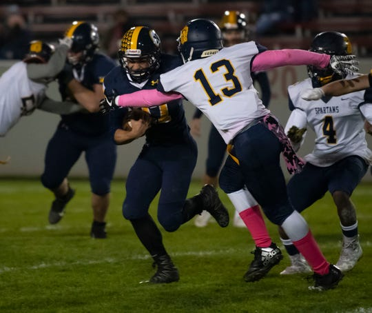 Port Huron Northern's Isaak Ullenbruch runs up the field as Fitzgerald's Devin Hogan tries to stop him during their football game Friday Oct. 25 at Memorial Stadium in Port Huron.