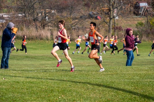 St. Clair junior Jack Pennewell (456) is chased by Armada's Noah Verlinde as they compete in the MHSAA Division 2 Boys Cross Country Regionals Saturday, Oct. 26, 2019, at Goodells County Park.
