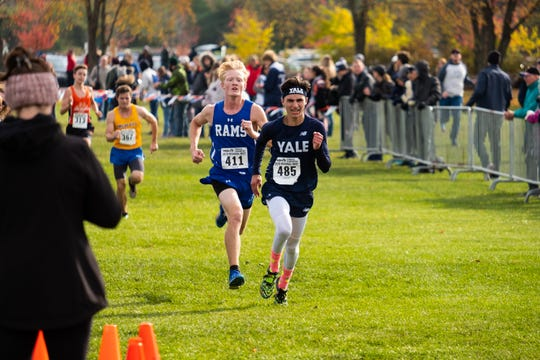 Yale's Colton Smith (485) is chased to the finish line as he competes in the MHSAA Division 2 Boys Cross Country Regionals Saturday, Oct. 26, 2019, at Goodells County Park.