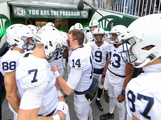 Penn State quarterback Sean Clifford (14) leads his team onto the field prior to a game against the Michigan State Spartans at Spartan Stadium.