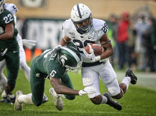 Oct 26, 2019; East Lansing, MI, USA; Penn State Nittany Lions running back Devyn Ford (28) is tackled by Michigan State Spartans safety David Dowell (6) during the first half of a game  at Spartan Stadium. Mandatory Credit: Mike Carter-USA TODAY Sports