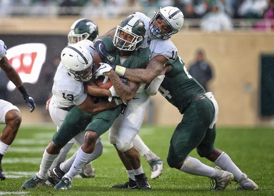 Oct 26, 2019; East Lansing, MI, USA; Michigan State Spartans wide receiver Tre Mosley (17) is tacked by Penn State Nittany Lions linebacker Ellis Brooks (13) and Penn State Nittany Lions linebacker Micah Parsons (11) during the first half of a game at Spartan Stadium. Mandatory Credit: Mike Carter-USA TODAY Sports