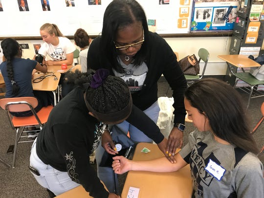 Wilhelmina Sizer, a nurse practitioner, teaches Autumn Wilson how to take Grace Reese's blood pressure. Sizer is a member of the Rochester Black Nurses Association.