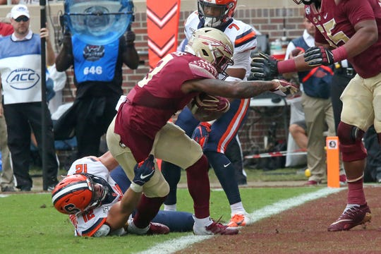 Florida State's Cam Akers, center, breaks the tackle of Syracuse's Andrew Armstrong to score during the first quarter of an NCAA college football game, Saturday, Oct. 26, 2019, in Tallahassee Fla.