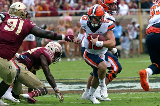 Syracuse's Tommy DeVito, right, tries to run around Florida State's Robert Cooper during the first quarter of an NCAA college football game, Saturday, Oct. 26, 2019, in Tallahassee Fla.