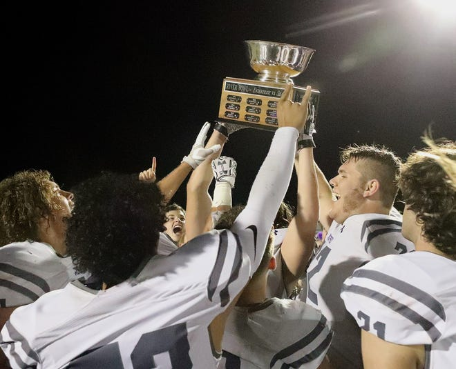 Shasta High football players hoist the River Bowl trophy to celebrate their 38-26 victory over Enterprise on Friday, Oct. 25, 2019.