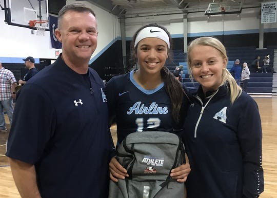 Airline's Gabby Patronis holds her Times Athlete of the Week backpack between coaches Scott Parson and Reggie Digilormo.